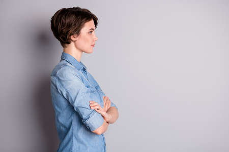 Profile photo of attractive business lady groomed wavy bobbed hairdo arms crossed self-confident chief worker look side empty space wear casual denim shirt isolated grey color background