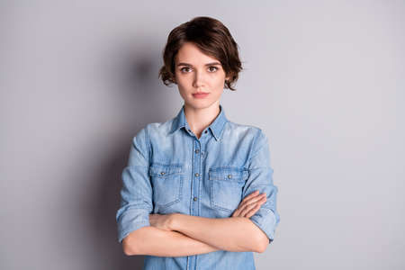 Photo of attractive business lady groomed wavy bobbed hairdo arms crossed self-confident chief worker wear casual denim shirt isolated grey color background