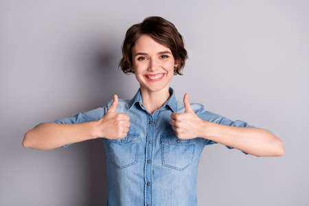 Photo of attractive lady wavy hairdo hold thumb fingers raised up express agreement confident smile cheerful person wear casual denim shirt isolated grey color background