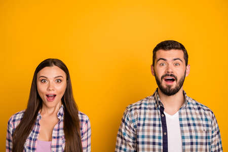 Closeup photo lady guy couple stand close together listen good news open mouth crazy facial expressions emotions wear casual plaid shirts outfit isolated yellow color background