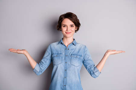 Photo of attractive lady hold open arms hands empty space showing nice offer two variants pick select best one wear casual denim shirt isolated grey color background Stock Photo