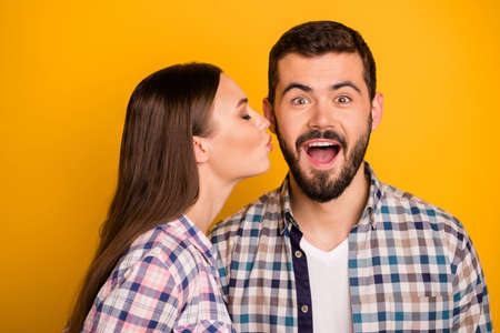 Closeup photo amazed guy couple stand close together open mouth pretty lady kissing his cheekbone crazy facial expression wear casual plaid shirts outfit isolated yellow color background