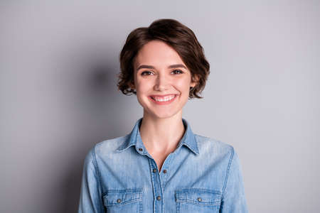 Closeup photo of attractive cheerful business lady perfect wavy bobbed hairdo smiling white teeth friendly person wear casual denim shirt isolated grey color background Фото со стока