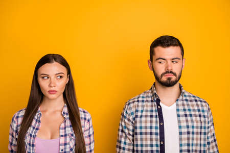 Closeup photo pretty lady handsome guy couple stand keep distance not smiling look eyes suspicious responsible people citizens wear casual plaid shirts isolated yellow color background Stock Photo