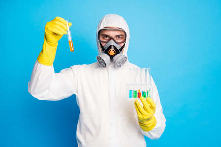Portrait of confident chemist in white hazmat suit hold test-tube experimental vaccine covid infection wear yellow latex gloves goggles breathing mask isolated over blue color background