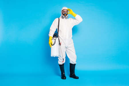 Full length photo of doctor man in biological protective uniform ready stop ncov infection epidemic spread have spray equipment isolated over blue color background