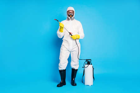 Full body photo of confident medical worker man hold spray equipment ready protect people ncov infection epidemic wear biological suit uniform boots isolated blue color background