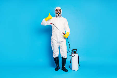 Full size photo medical worker man approve covid stop epidemic equipment disinfection show thumb-up sign wear white uniform latex yellow gloves goggles isolated blue color background Reklamní fotografie