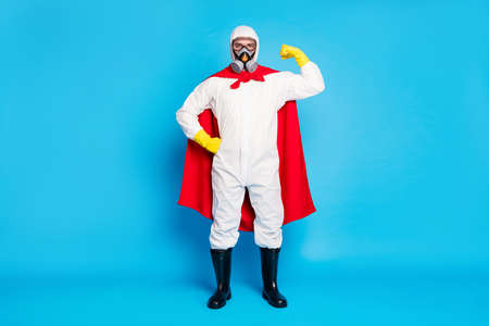 Full length photo strong doctor man show muscles power stop biological danger covid epidemic spread wear yellow latex gloves goggles white suit red mantle isolated blue color background