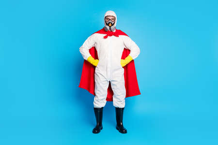 Full size photo of serious medical worker put hands waist ready stop ncov infection spread wear red superhero costume red cape boots latex gloves goggles isolated blue color background Reklamní fotografie