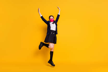 Full size photo of high school student girl jump enjoy covid-19 quarantine wear black blazer jacket long socks skirt medical mask isolated over bright shine color background