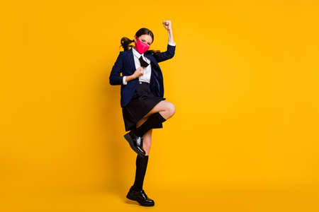 Full length body size view of her she nice attractive lucky schoolgirl jumping rejoicing accomplishment attainment wearing mask isolated over bright vivid shine vibrant yellow color background