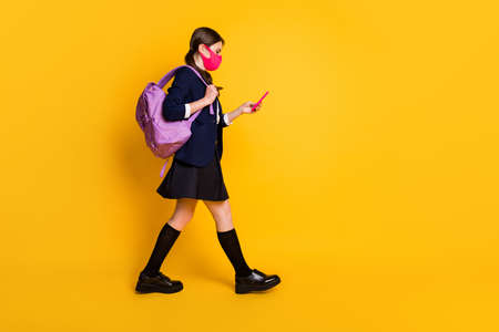 Full body profile side photo high school student girl go walk lesson use smartphone wear black blazer jacket skirt long socks backpack medical mask isolated yellow color background