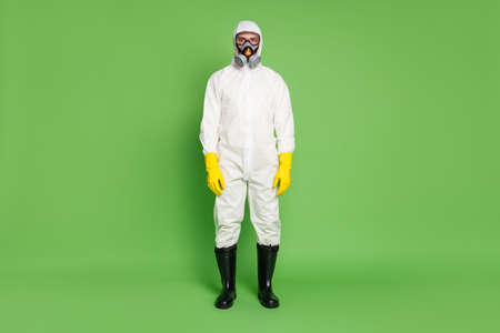 Full length body size view of his he nice serious expert workman wearing gas mask white sterile costume sars ncov n-cov-2 defense public place isolated over green pastel color background Stock Photo