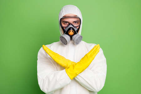 Close-up portrait of his he nice serious disinfectant wearing gas mask showing stop sign quarantine keep social distance self isolation stay home isolated over green pastel color background Reklamní fotografie