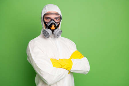 Close-up portrait of his he nice content serious professional disinfectant wearing gas mask anti viral pollution radiation quarantine folded arms isolated over green pastel color background