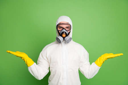 Portrait of his he nice professional disinfectant workman wearing gas mask holding on two palms copy space quarantine restrictions choose choice decide isolated over green pastel color background Banque d'images