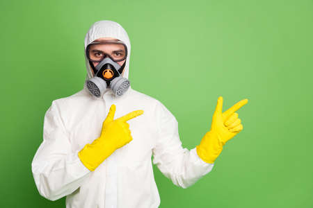 Close-up portrait of his he nice serious confident professional disinfectant wearing gas mask showing copy empty blank place feedback space isolated over green pastel color background