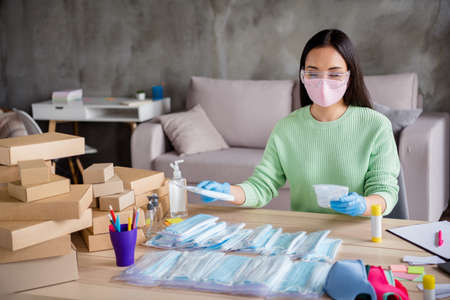 Photo of lady hands latex gloves business organize order face medical masks handmade package sorting carton boxes online delivery shop commerce manager home office indoors Standard-Bild
