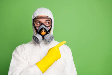 Close-up portrait of his he nice experienced skilled professional disinfectant doctor doc wearing gas mask showing solution way direction copy space isolated over green pastel color background Reklamní fotografie