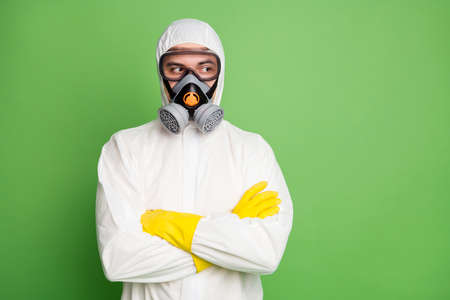 Portrait of his he nice serious content professional disinfectant specialist wearing gas mask equipment folded arms rescue service isolated over green pastel color background
