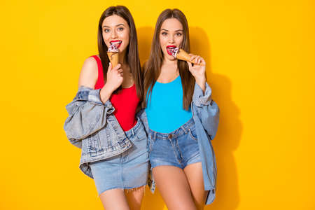 Portrait of positive cheerful sisters girls have fun eat lick delicious icecream wear jeans singlet isolated over bright color background