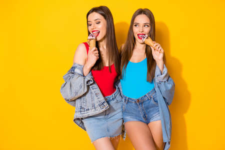 Portrait of nice attractive lovely pretty stunning charming cheerful girlish funny brown-haired girls embracing eating icecream isolated on bright vivid shine vibrant yellow color background