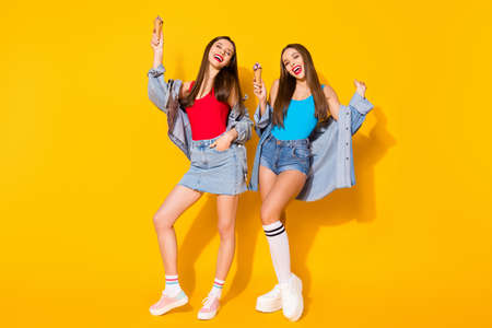 Full length photo positive cheerful funky girls sisters have fun spring time weekend holiday hold ice cream cones wear blue red tank-top denim isolated bright shine color background