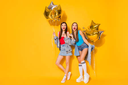 Full length body size view of nice attractive cool fashionable cheerful cheery, girls holding in hands air balls having fun isolated on bright vivid shine vibrant yellow color background Imagens
