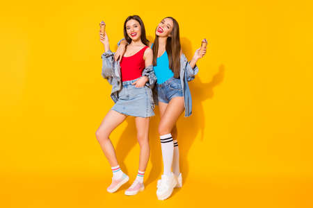 Full body photo positive cheerful girls sisters youth enjoy spring time weekend hold tasty icecream scoops wear red blue tank-top denim legs long socks isolated bright shine color background
