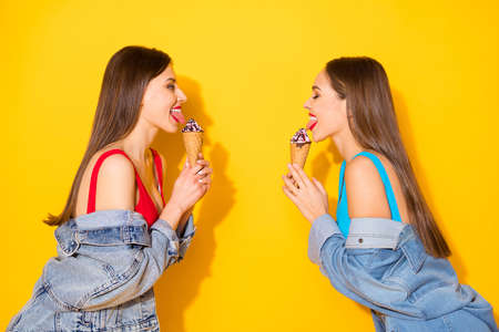 Profile side view portrait of her she nice attractive lovely pretty cheerful cheery haired girls licking icecream having fun isolated on bright vivid shine vibrant yellow color background