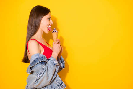 Profile side view portrait of her she nice attractive lovely cute winsome cheerful cheery girlish haired girl licking icecream having fun isolated on bright vivid shine vibrant yellow color background