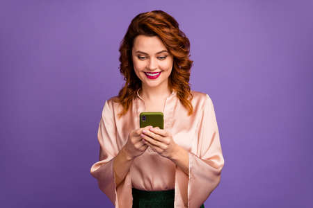 Photo of charming pretty chic foxy lady hold telephone hands toothy smiling got party invitation message wear luxury beige shirt blouse isolated purple color background Banco de Imagens