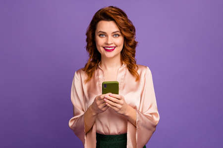 Photo of charming chic classy lady hold telephone hands toothy smiling, got party invitation message good mood wear luxury beige shirt blouse isolated purple color background