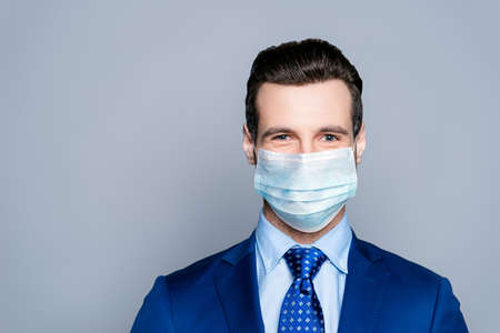 Close-up portrait of his he nice attractive imposing chic classy cheery guy corporate partner wearing medical gauze mask sars-ncov-s prevention isolated over grey pastel color background Standard-Bild
