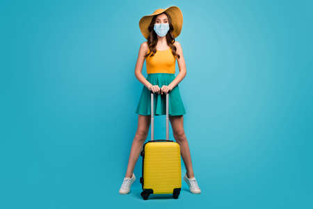 Full length body size view of her she pretty lady traveler hold rolling case railway bus station check-in open destination border wear mask isolated bright vivid shine vibrant blue color background