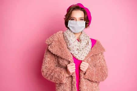 Portrait of her she attractive pretty fashionable lovely girl wearing gauze mask faux fur overcoat influenza prevention sars risk co2 environment isolated on pink pastel color background Foto de archivo