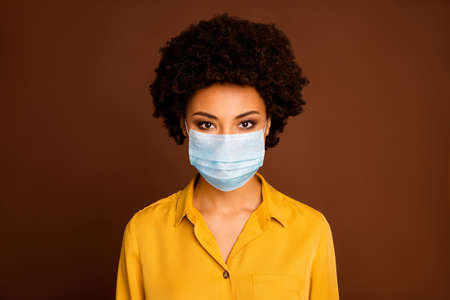 Close-up portrait of her she pretty dark skin wavy-haired lady wearing yellow shirt blouse gauze mask concept sickness illness disease life sars cov ncov prevention isolated on brown color background