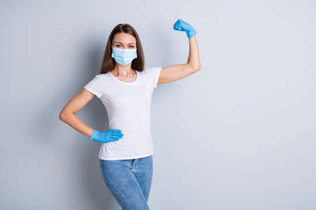 Photo of cool lady raise fist demonstrate strong immune system sport save world not afraid corona virus covid wear latex gloves protect face mask isolated grey color background