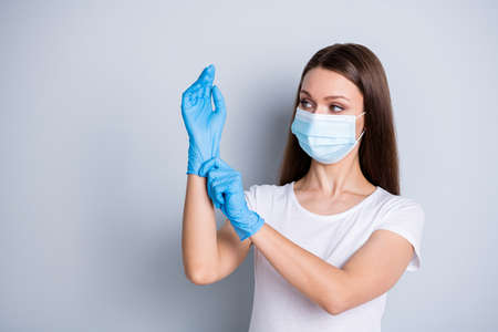 Photo of citizen responsible lady keep social distance crowd people hospital examination put on gloves hundred per cent protection concept wear face mask isolated grey color background