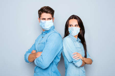 Serious man and woman with crossed hands standing back to back after quarrel wear medical safety sterile mask on face, social distance pandemic corona virus prevention protection concept covid19