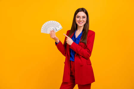 Successful banker girl hold use money fan point finger recommend cashback income deposit payment wear red blazer jacket suit style stylish trendy isolated bright shine yellow color background