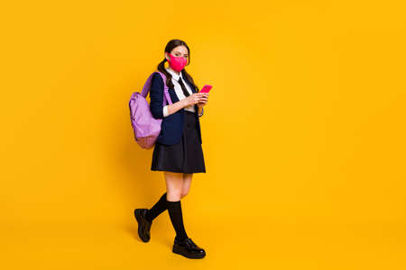 Full length photo of high student girl use cellphone interested social media covid-19 quarantine news wear black jacket blazer long socks skirt isolated over bright shine color background