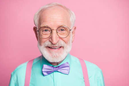 Closeup photo of amazing stylish clothes grandpa positive facial expression smile wear specs mint shirt suspenders violet bow tie isolated bright pink pastel color background
