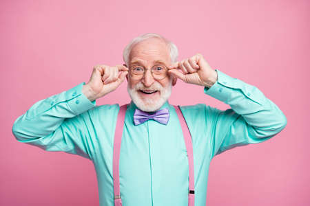 Photo of excited attractive grandpa good mood holding hands on specs glad nice eyesight wear mint shirt suspenders bow tie isolated pastel pink color background