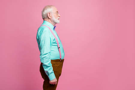 Profile photo of attractive grandpa looking empty space concentrated focused not smiling wear specs mint shirt suspenders bow tie pants isolated pink pastel color background 写真素材