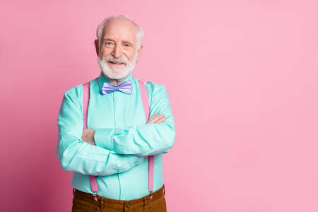 Photo of amazing stylish clothes grandpa arms crossed positive facial expression smile wear mint shirt suspenders violet bow tie isolated bright pink pastel background