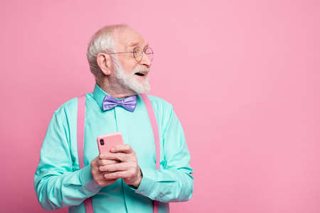Really i get like. Excited pensioner ask granddaughter using social media network hold smartphone impressed look copyspace wear turquoise outfit purple bow tie isolated pastel pink color background