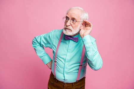 Photo d'un grand-père attrayant tenir la main près de l'oreille en écoutant des rumeurs focalisées sur un bavardage une mauvaise personne porter des spécifications de chemise à la menthe bretelles noeud papillon pantalon isolé sur fond de couleur pastel rose Banque d'images