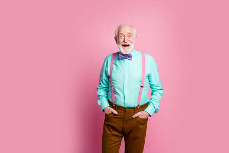 Photo of funny aged grandpa good mood standing self-confident hands pockets open mouth wear mint shirt suspenders bow tie brown pants isolated pink pastel background